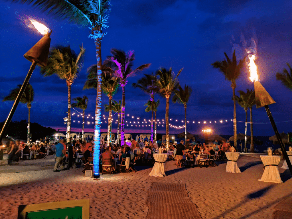 Event on the beach with tiki torches and palm trees