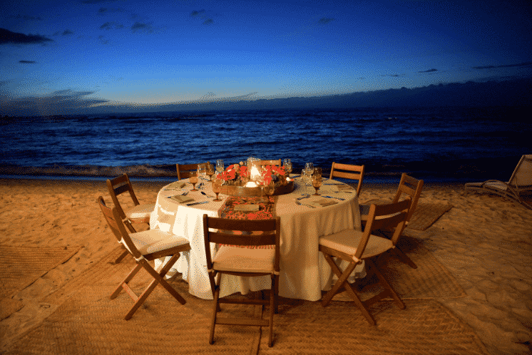 A fancy dining table set up on the beach.