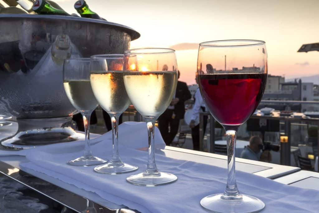 Four wine glasses on an outdoor bar.