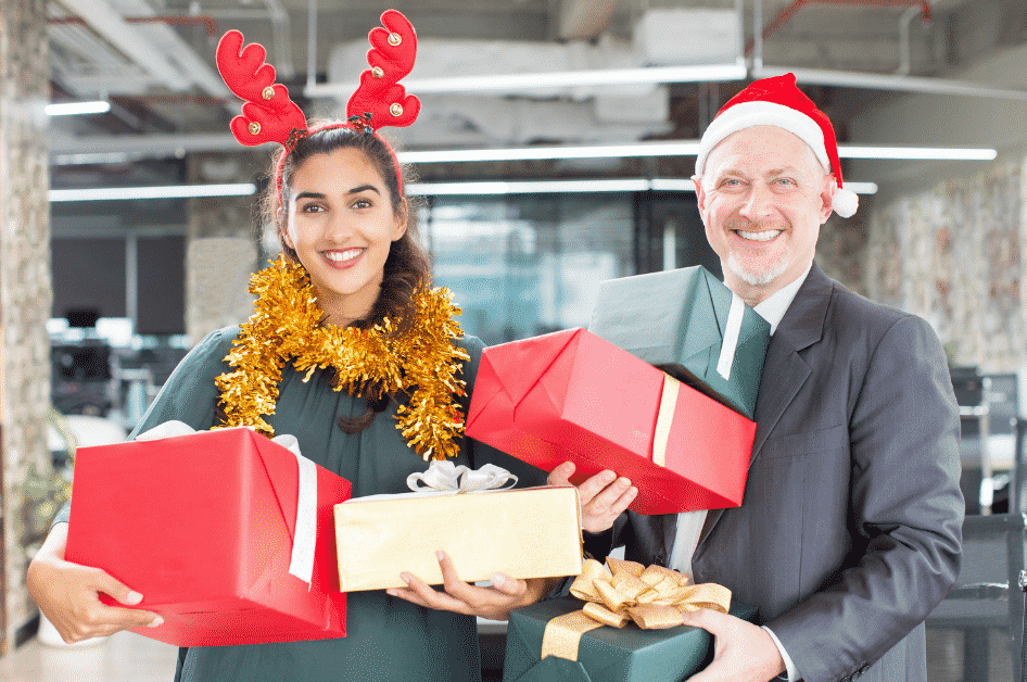A man and woman in holiday hats holding wrapped gifts.